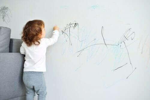 barn der tegner på væg
