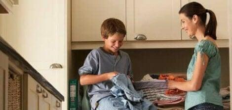 dreng der hjælper sin mor med vasketøj