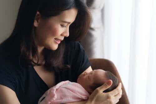 mor med lille baby i armene
