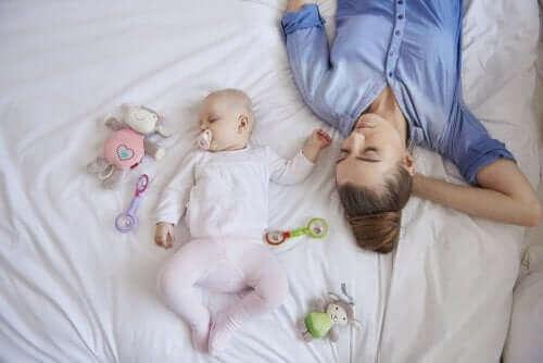 mor og baby der sover i seng