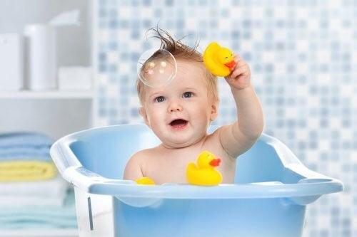 Baby leger med gule badeænder i badekarret