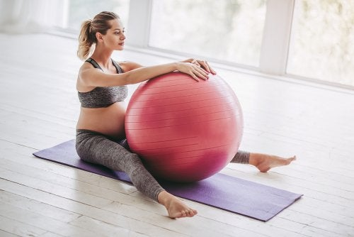 gravid kvinde der træner med bold