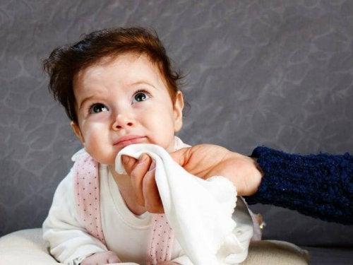 lille barn der bliver tørret om munden