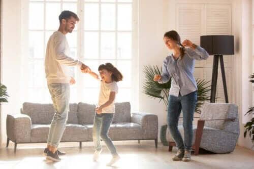 Far, mor og datter danser sammen i stuen