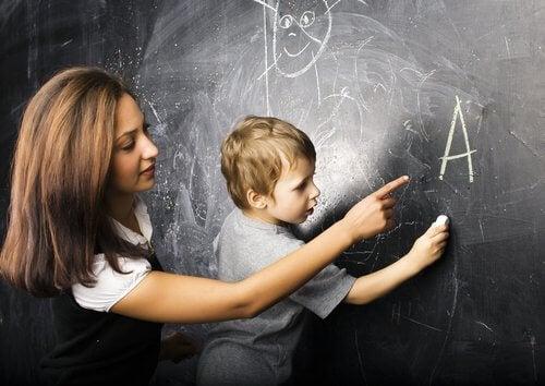 lærer der hjælper barn med at skrive på tavle