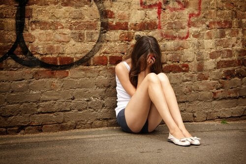 ung, trist kvinde, der sidder op ad væg