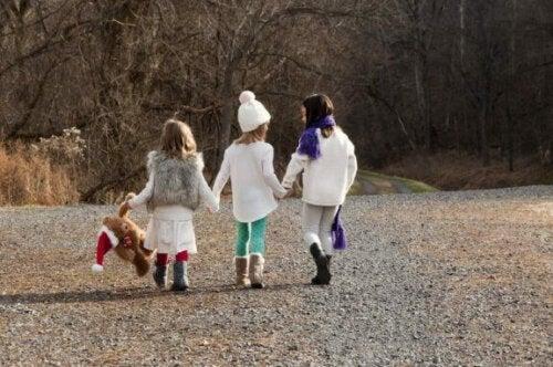 3 børn der holder i hånd udenfor
