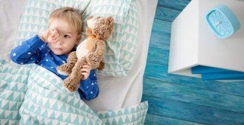 barn der ligger i seng med en bamse