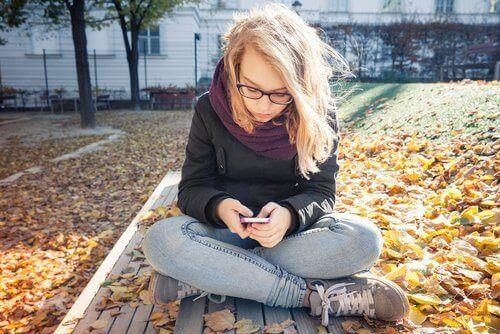 ung kvinde der bruger sin mobil udenfor