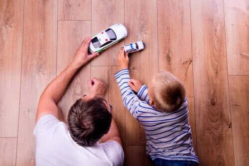 far og søn der leger med biler