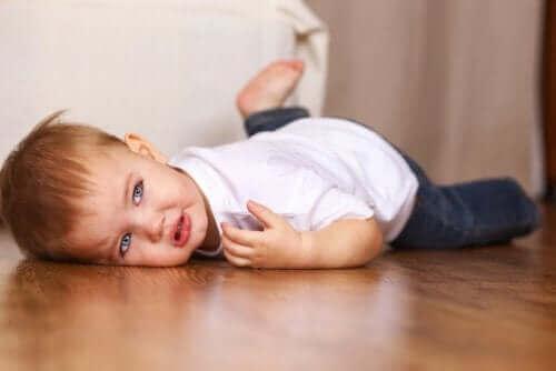 lille dreng der ligger på gulv