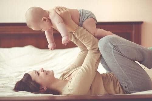 mor der leger med sin baby i seng