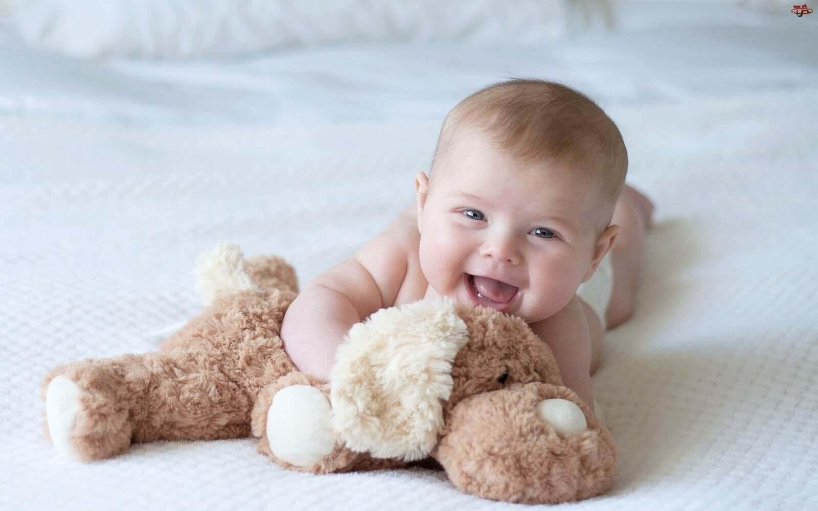 Dåbsgaveideer: Baby griner med bamse.