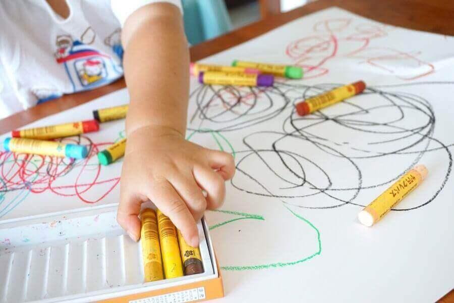 Sådan tolkes farver i børns tegninger: Barn tegner med forskellige farvekridt.