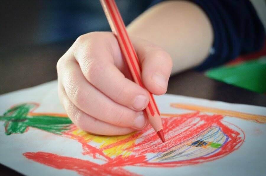 Barn tegner med rød farveblyant på farverig tegning.