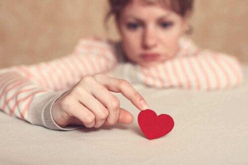 kvinde der holder et hjerte med sin finger