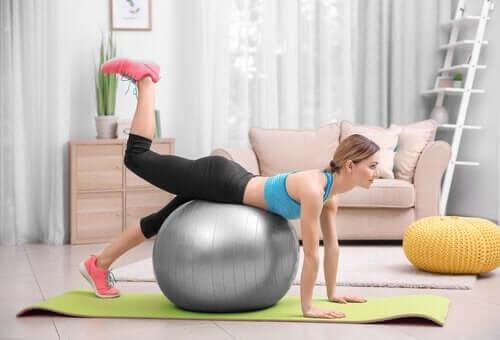 Kvind træner med motionsbold efter fødslen.
