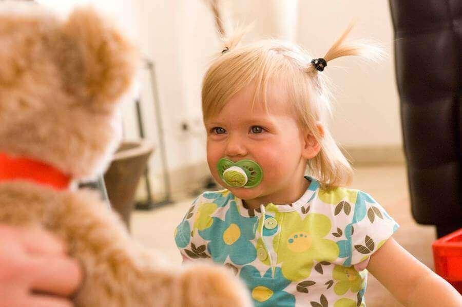 Lille pige med sut og bamse.