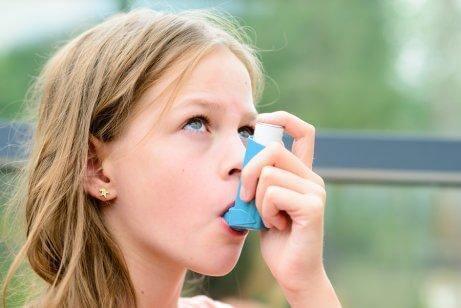 Pige bruger sin inhalator mod astma.