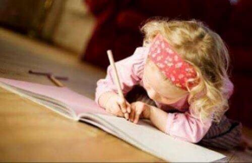 Forfatterbørn: Lille pige ligger på gulvet og skriver i notesbog.