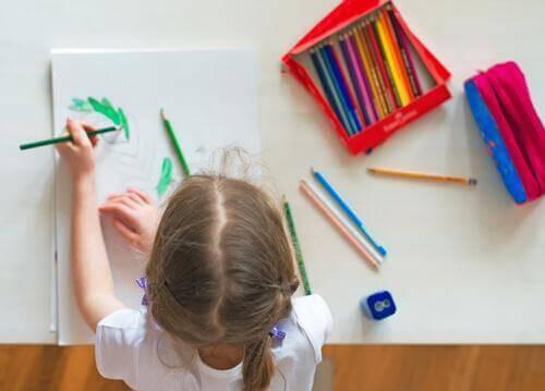 Pige sidder og tegner ved sit skrivebord.