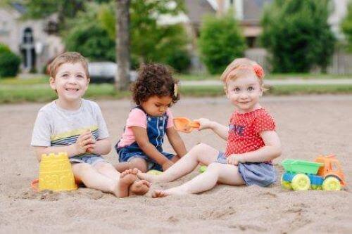 Sociale færdigheder: Små børn leger sammen i sandkasse.