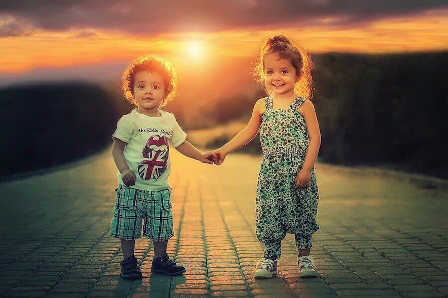 Børn føler beskedenhed. Lille pige og dreng holder i hånden.