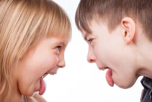 Børn rækker tunge af hinanden.
