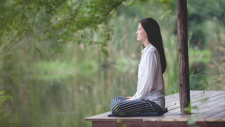 Kvinde meditere ved sø. Jeg vil være mor, men jeg er bange
