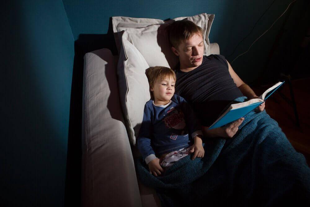 Sådan fortæller du dine børn uhyggelige historier. Far læser højt for sin søn.