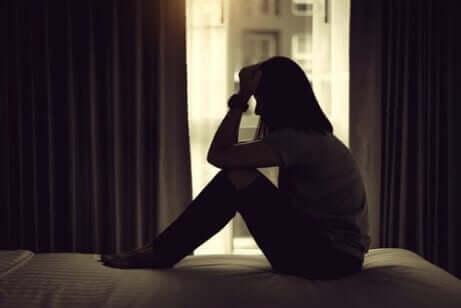Tips til forebyggelse af depression efter adoption: Kvinde sidder fortvivlet på en seng i et mørkt soveværelse.