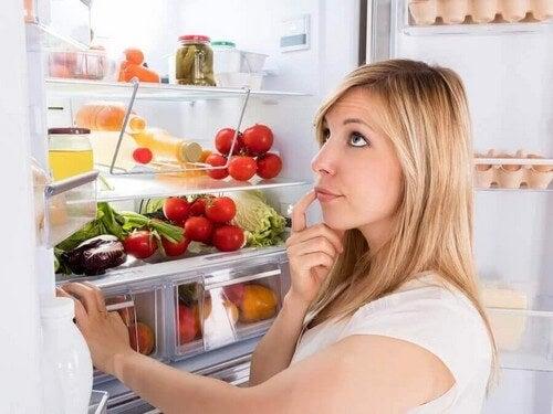 Kvinde står og tænker ved køleskabet