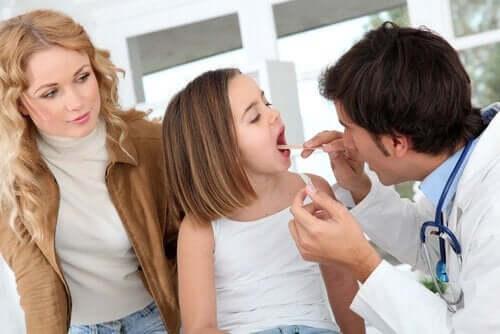 Hvornår skal man fjerne mandlerne hos børn. Læge tjekker piges mund og mandler.