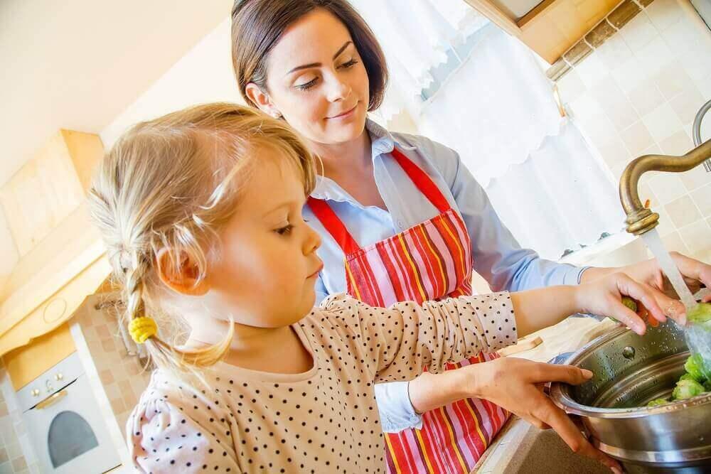 Sådan underholdes børn mens du laver mad. Lille pige skylder grøntsager.