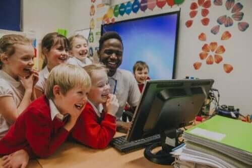 børn og underviser der griner af noget på computer