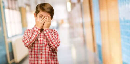 dreng med hænder foran ansigt