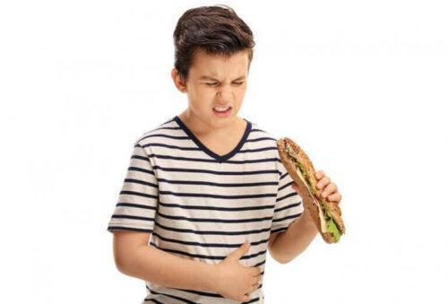 dreng med sandwich der har ondt i maven