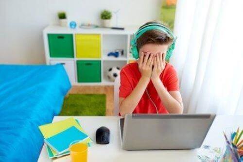 dreng ved computer der holder sig for øjnene