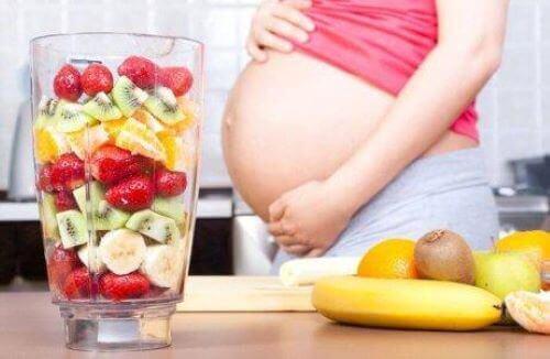 gravid kvinde der laver en stor smoothie