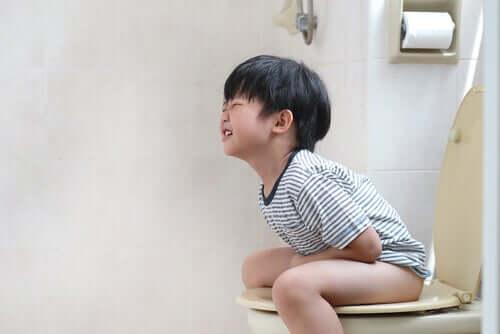 Lille dreng sidder på toilettet med forstoppelse.