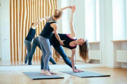kvinde der får hjælp til yogastilling