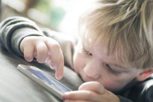 lille dreng der bruger en smartphone