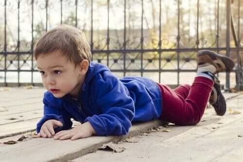 lille dreng der ligger på maven udenfor