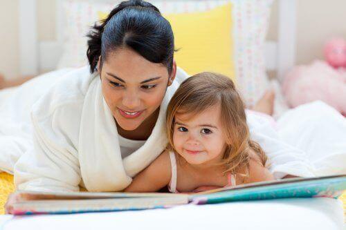 mor og datter der læser i seng