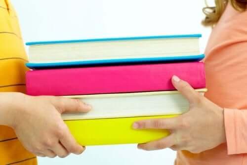 dreng og pige der holder en bunke bøger