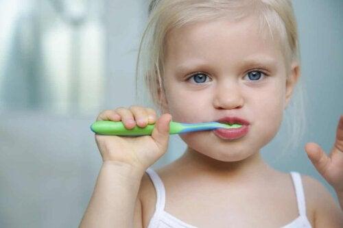 Pige børster tænder, men ofte skal man hjælpe børn med at børste tænder